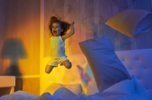 young-girl-jumping-on-bed