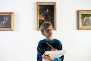 Young-boy-in-museum-with-notebook