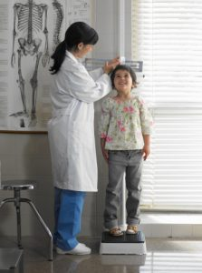 girl-standing-on-a-scale-being-examined-by-a-doctor