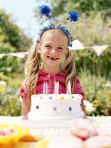 girl-with-no-teeth-holding-a-birthday-cake