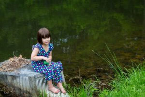 young-girl-sitting-by-a-river