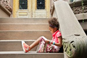 young-girl-sitting-on-steps-reading