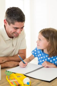 father-watching-daughter-write-in-journal
