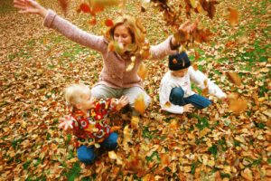 mother-with-two-children-jumping-in-leaves