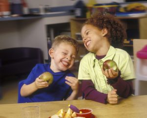 children-eating-apples-and-laughing