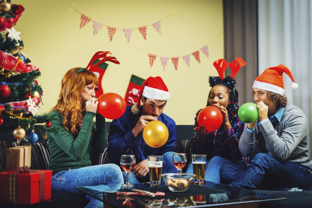 couples-blowing-up-holiday-balloons-wearing-party-hats