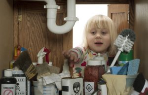 young-girl-reaching-for-chemicals-under-sink