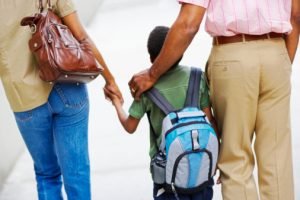young-boy-with-parents-and-backpack