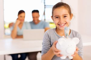 cheerful-little-girl-holding-piggybank