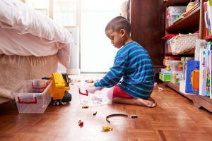 young-boy-sitting-on-floor-with-toys
