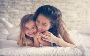 mother-and-daughter-in-bed-smiling-and-laughing