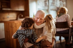 grandfather-hugging-grandkids-in-kitchen
