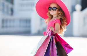 young-girl-with-blonde-hair-wearing-sunglasses-and-a-hat-carrying-shopping-bags