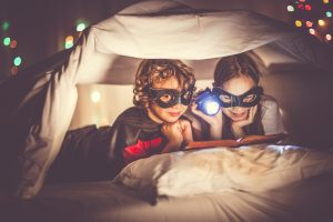 little-boy-and-little-girl-wearing-masks-reading-under-the-covers-with-a-flashlight