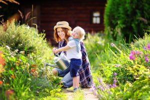 mother-and-young-boy-watering-plants-in-a-garden