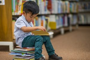 little-boy-sitting-on-stack-of-books
