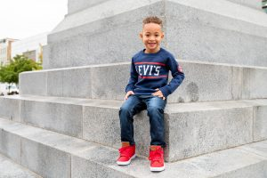 young-boy-sitting-on-ledge-smiling