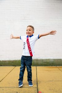 young-boy-standing-with-arms-wide-open-and-smiling