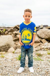 young-boy-standing-on-rocky-beach-with-hands-in-pockets